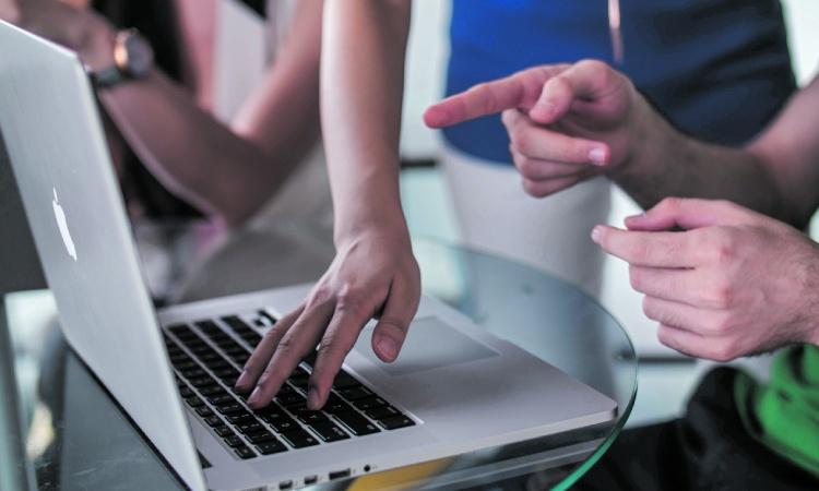 Diverses persones treballant amb un ordinador.