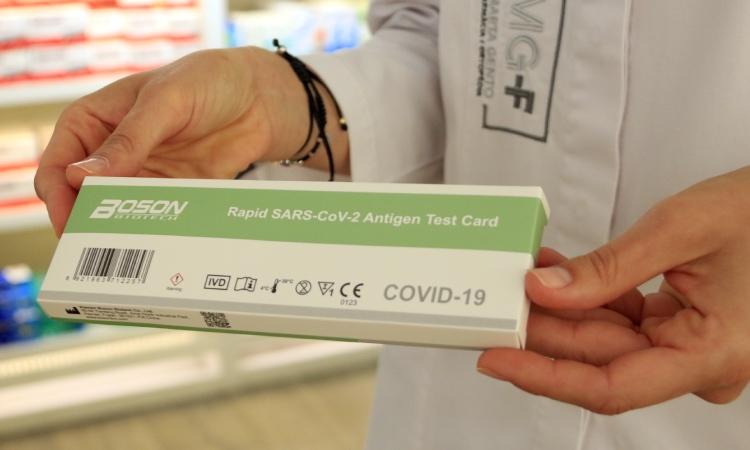 Una farmacèutica mostra un test d'antígens de Covid