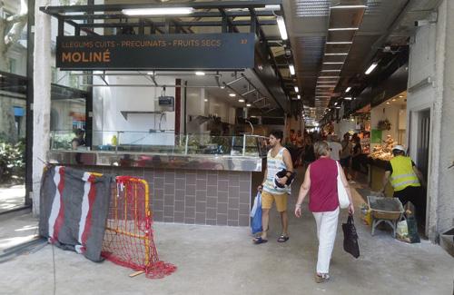 Imatge de clients del mercat entre els obrers, que continuen treballant per acabar els últims detalls. Foto: Línia Gràcia