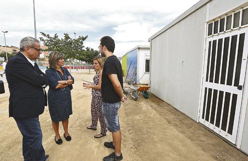 Visita de l'alcaldessa a l'escola amb els barracons de fons. Foto: Ajuntament